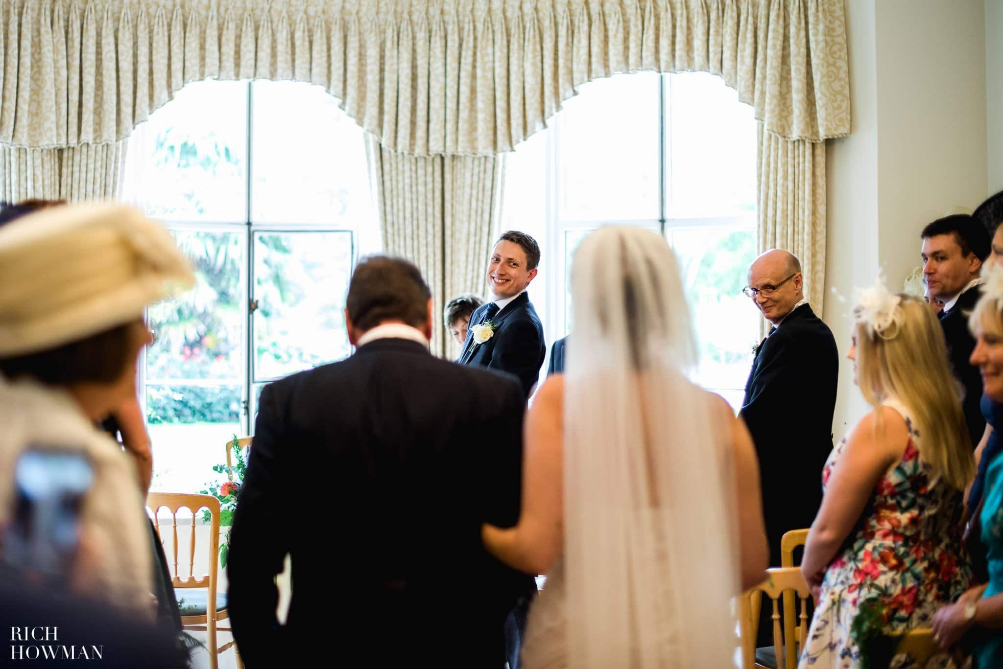 Groom glances over his shoulder at the bride as she walks down the aisle on her fathers arm