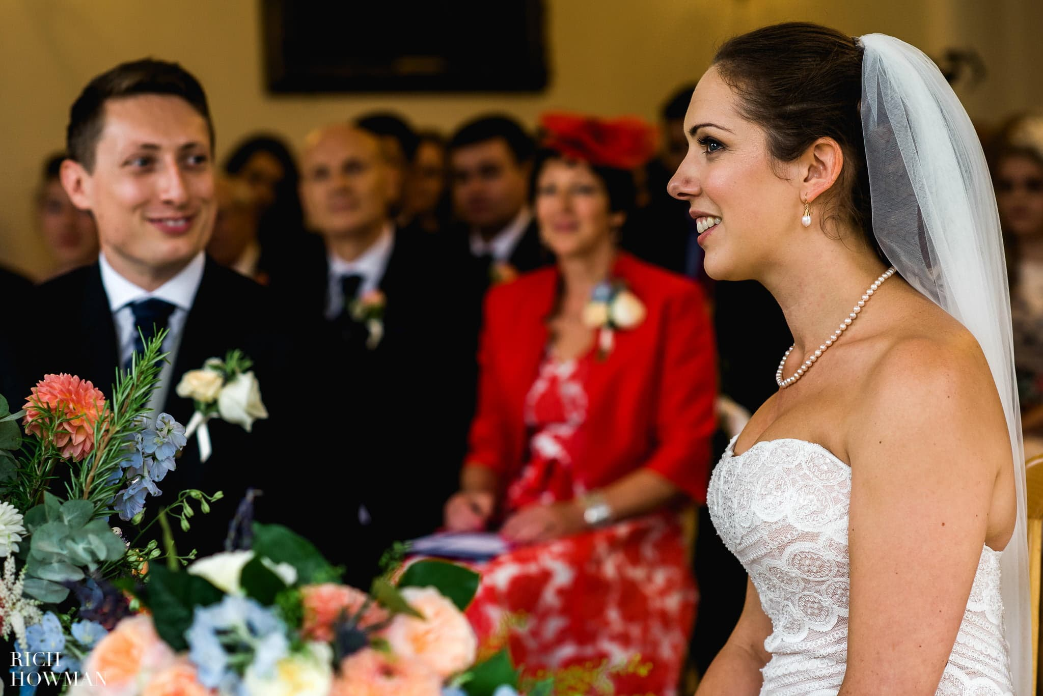 The groom looks at his new wife during their wedding ceremony at Cambridge Cottage in Kew Gardens.
