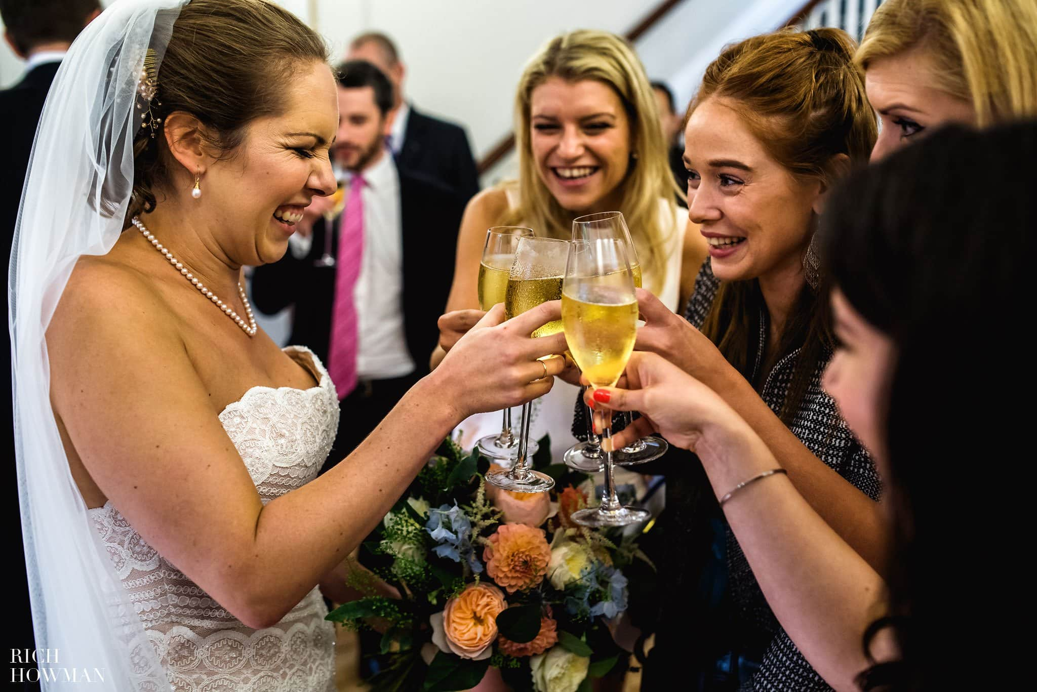 The brides friends share a glass of champagne with excited faces.