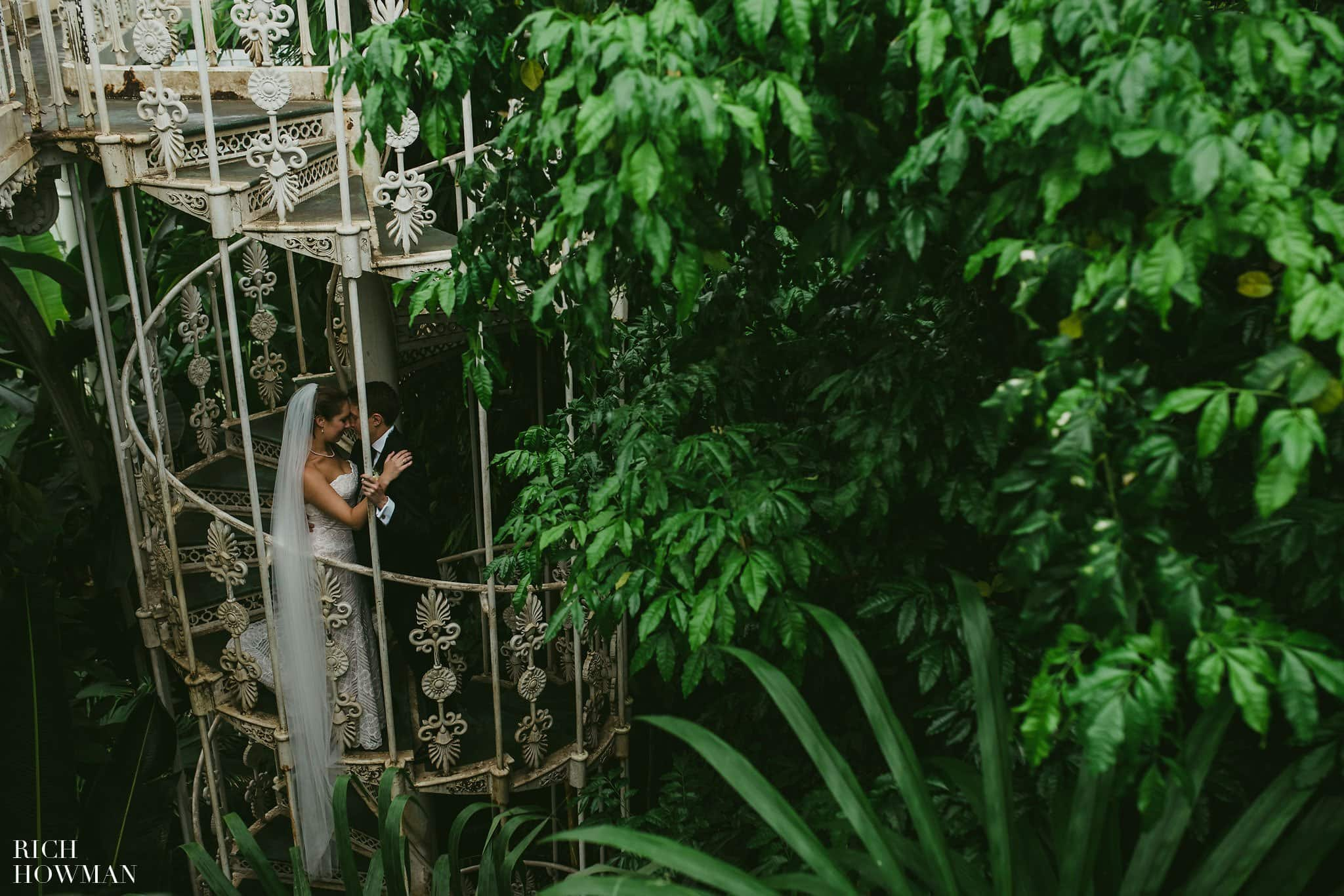 Bride and groom photographed on the Victorian spiral staircase in the Palm House during their wedding at Kew Gardens