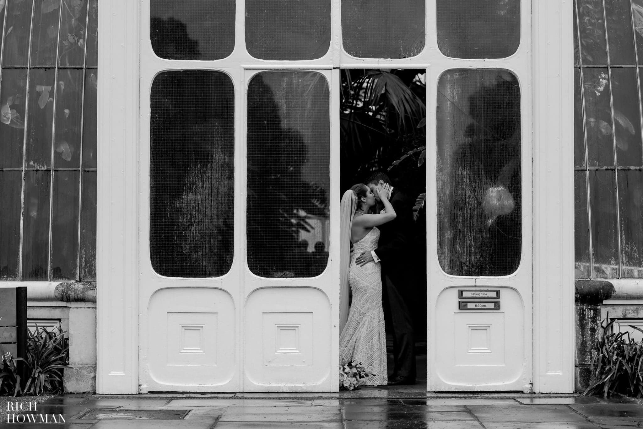 Black and white photo of the Bride and groom kissing outside the Palm House at Kew Gardens.