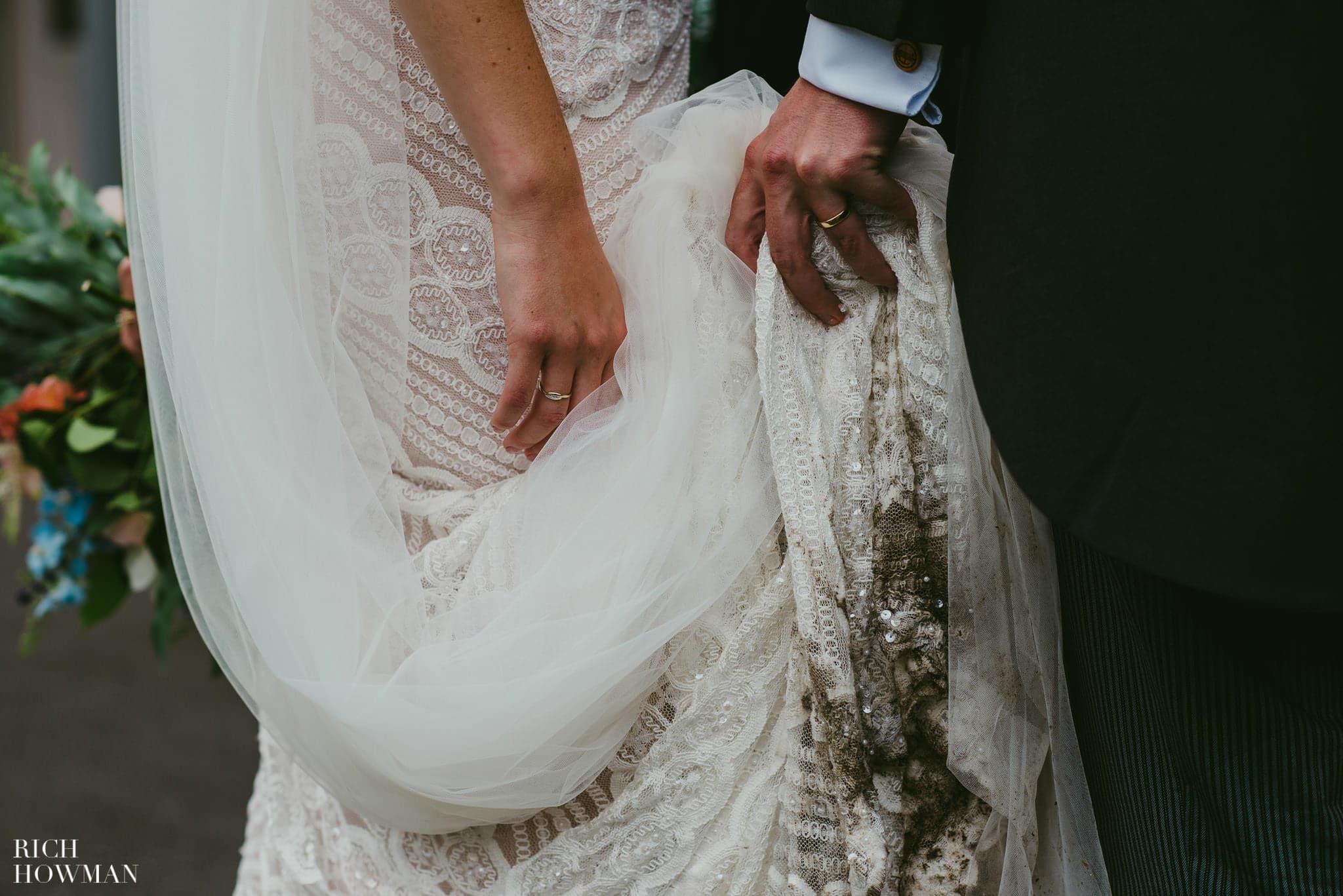 Hands holding up a dirty wedding dress.