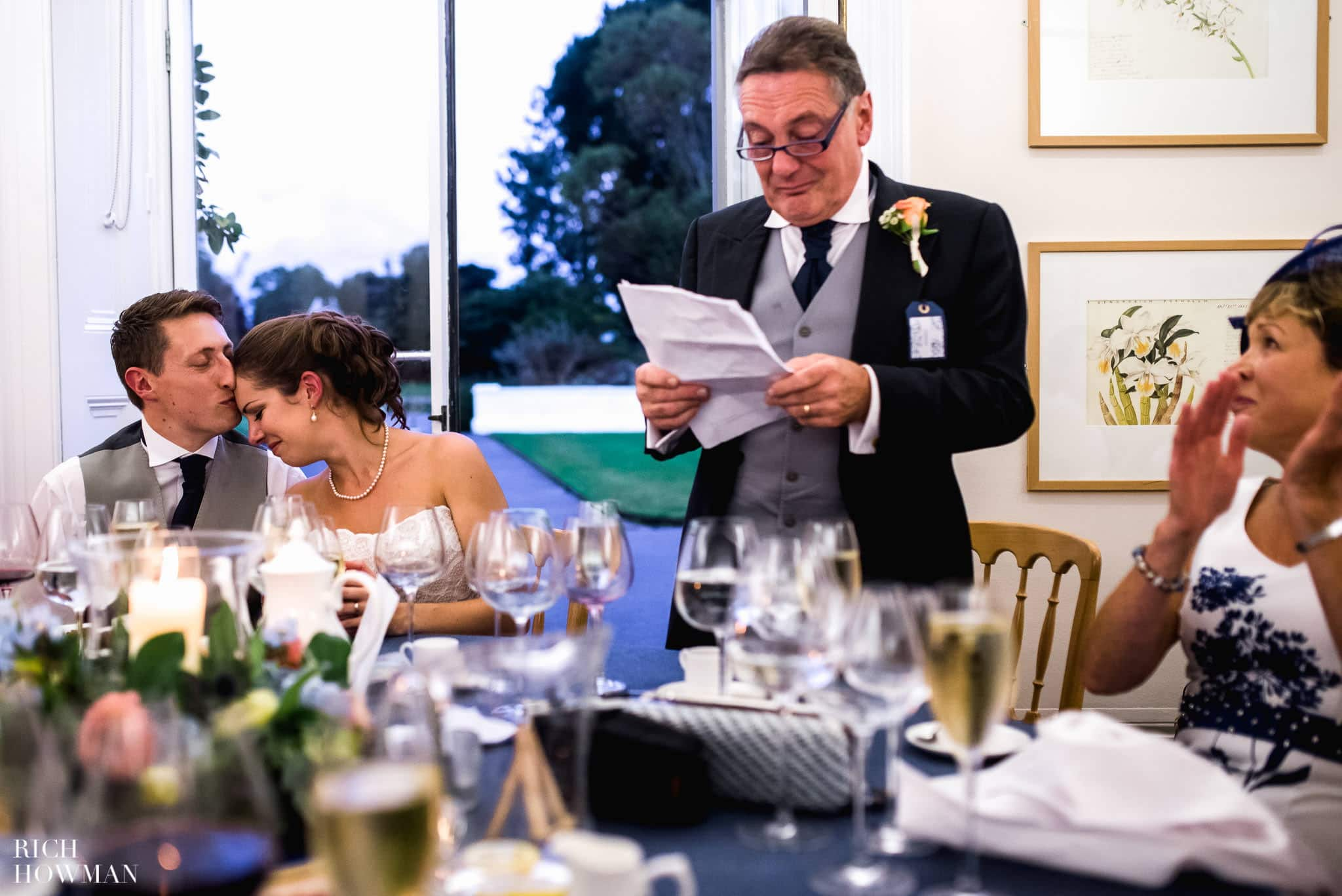 The brides father makes a speech whilst the groom comforts his new wife during their wedding reception at Cambridge Cottage in Kew