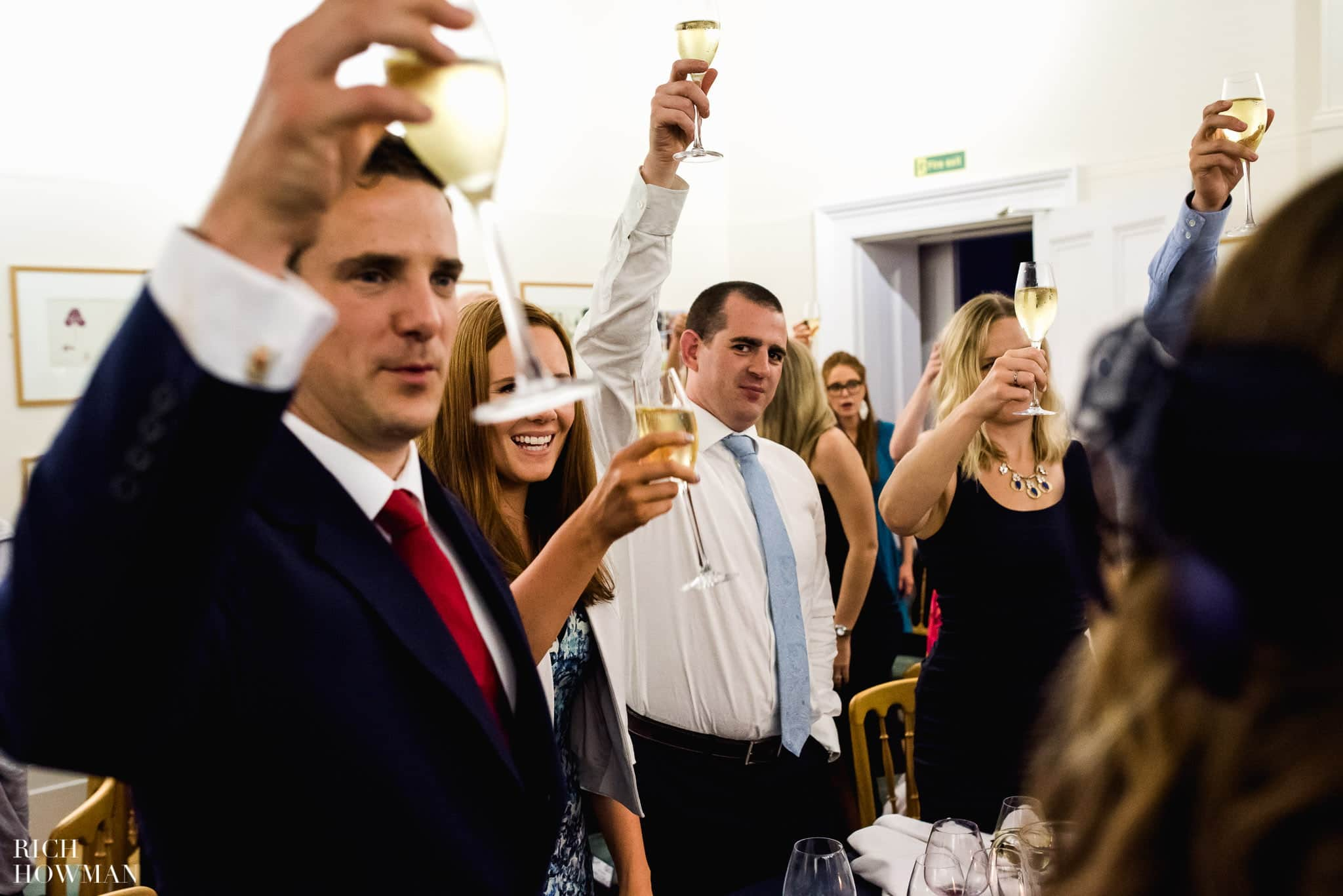 Wedding guests raise their glasses to toast the married couple at Cambridge Cottage