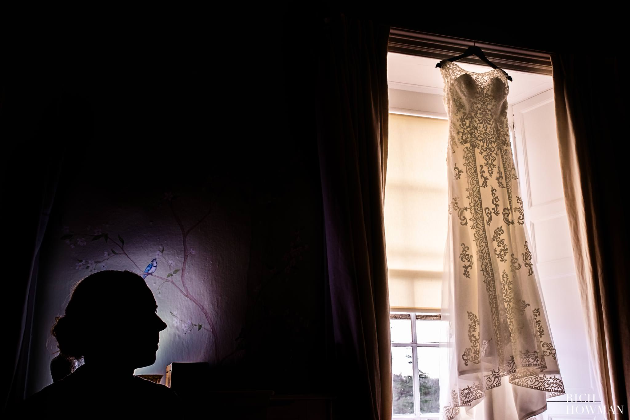 Relaxed wedding photographer at Pennard House, the bride looking at her wedding dress