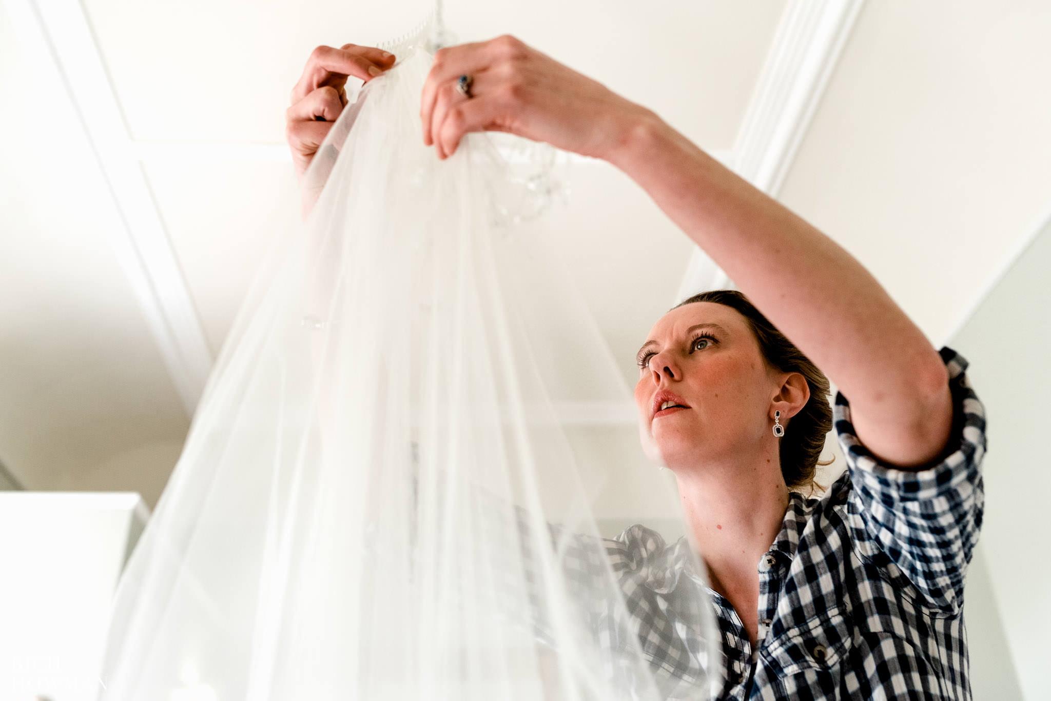 The bride adjusting her veil