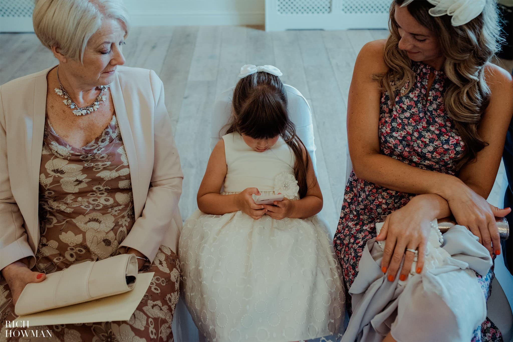 Photograph of a little girl playing with her phone at a wedding in Bradford on Avon