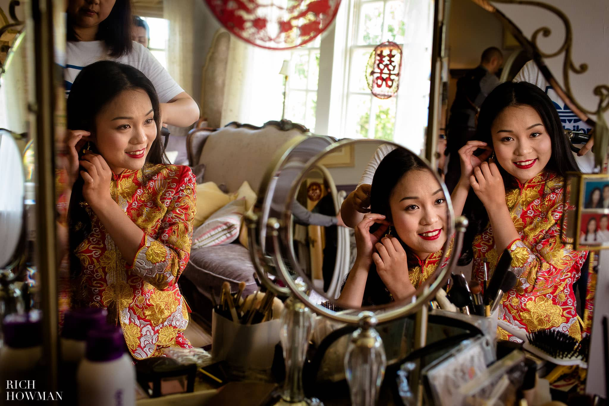 Chinese bride reflected in mirrors as she gets ready during her wedding at Brinsop Court
