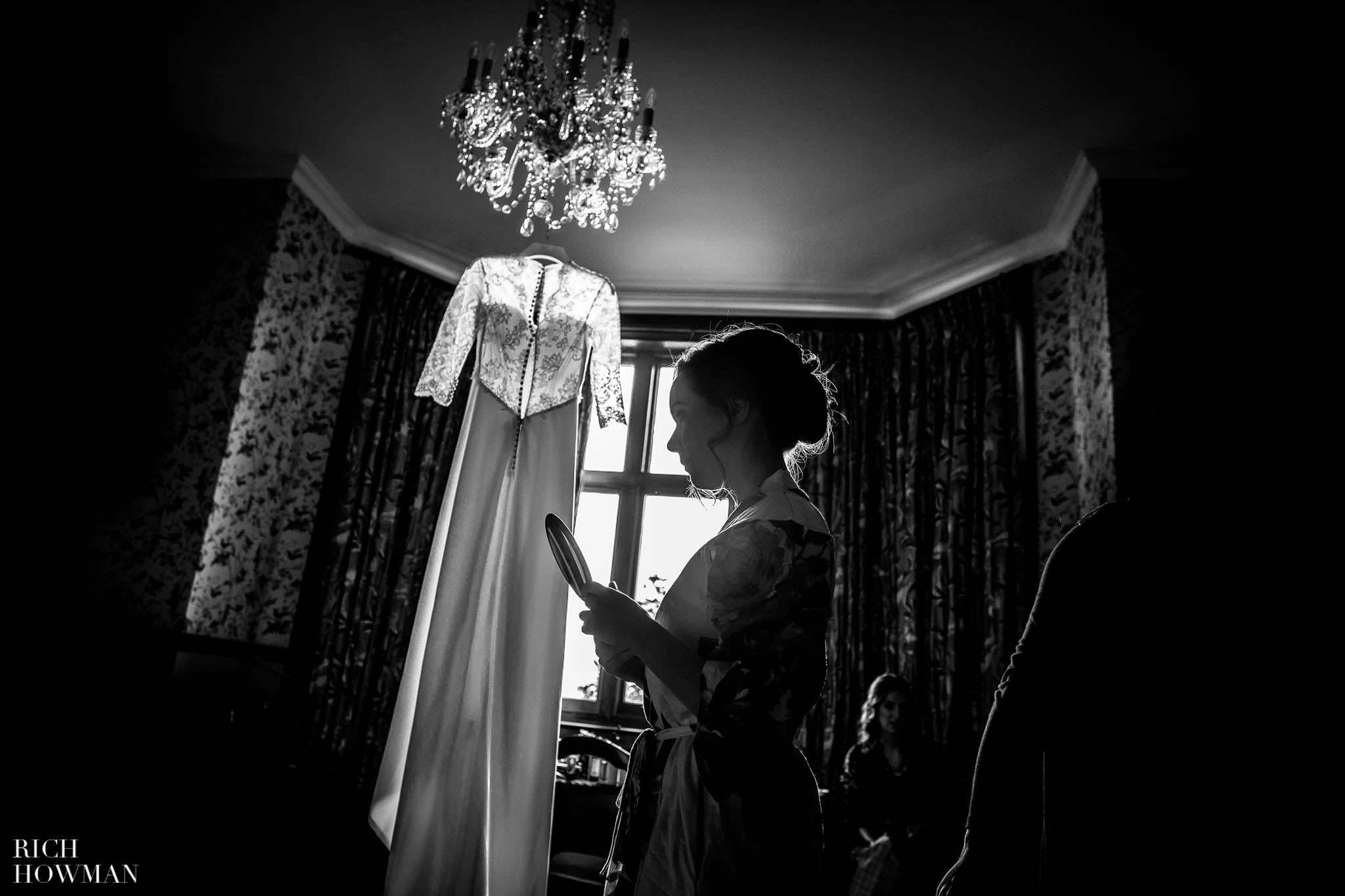 Black and white back-lit photo of the bride with her wedding dress