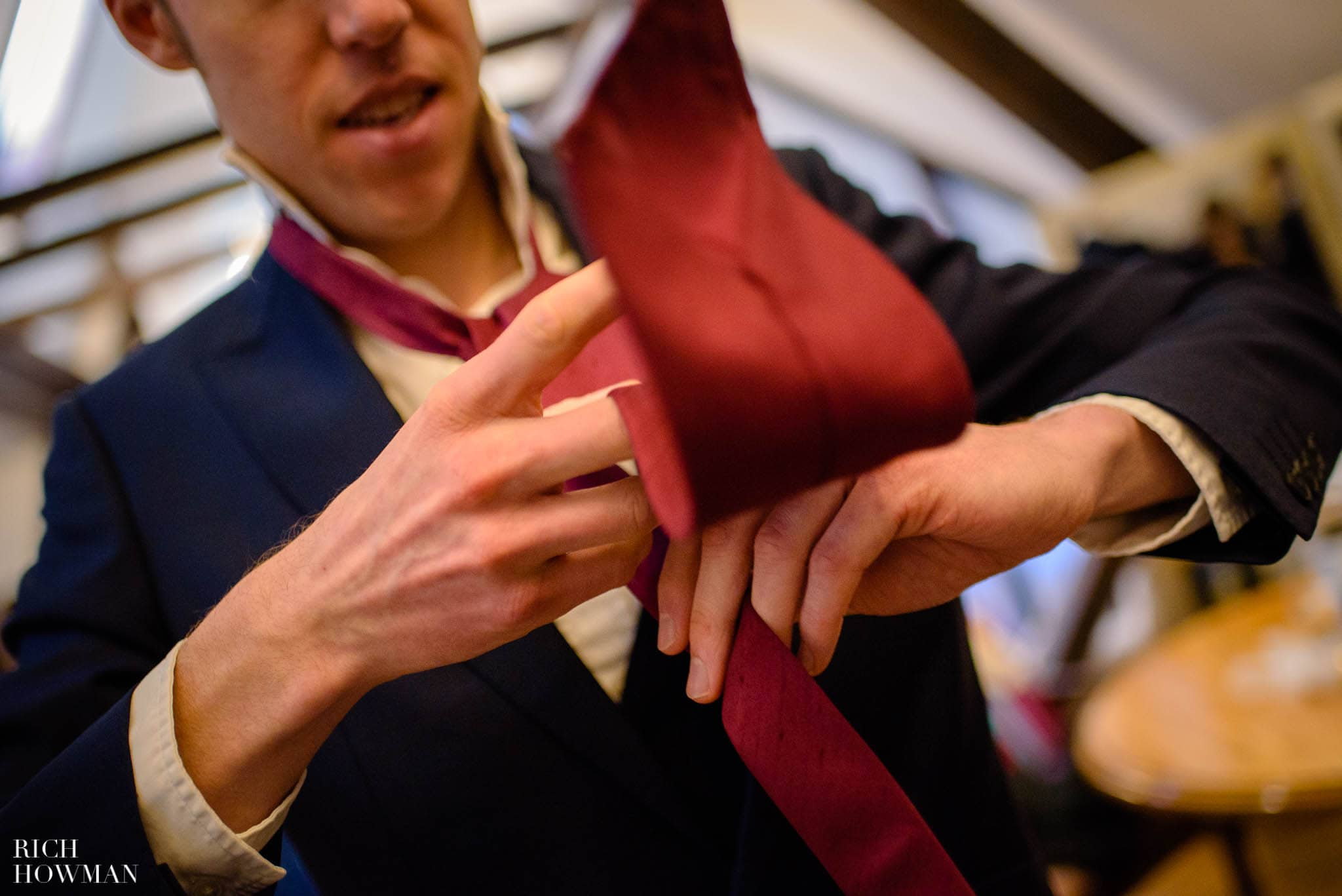 Groomsman putting on a red tie for a wedding at Huntsham Court