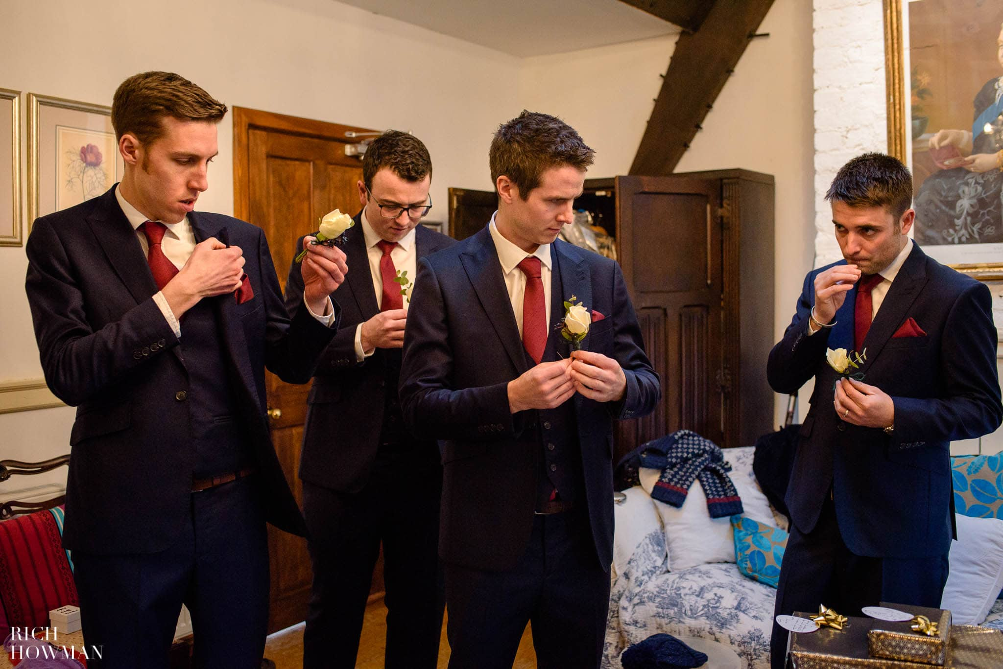 Groomsmen lined up putting on their wedding flowers at Huntsham Court