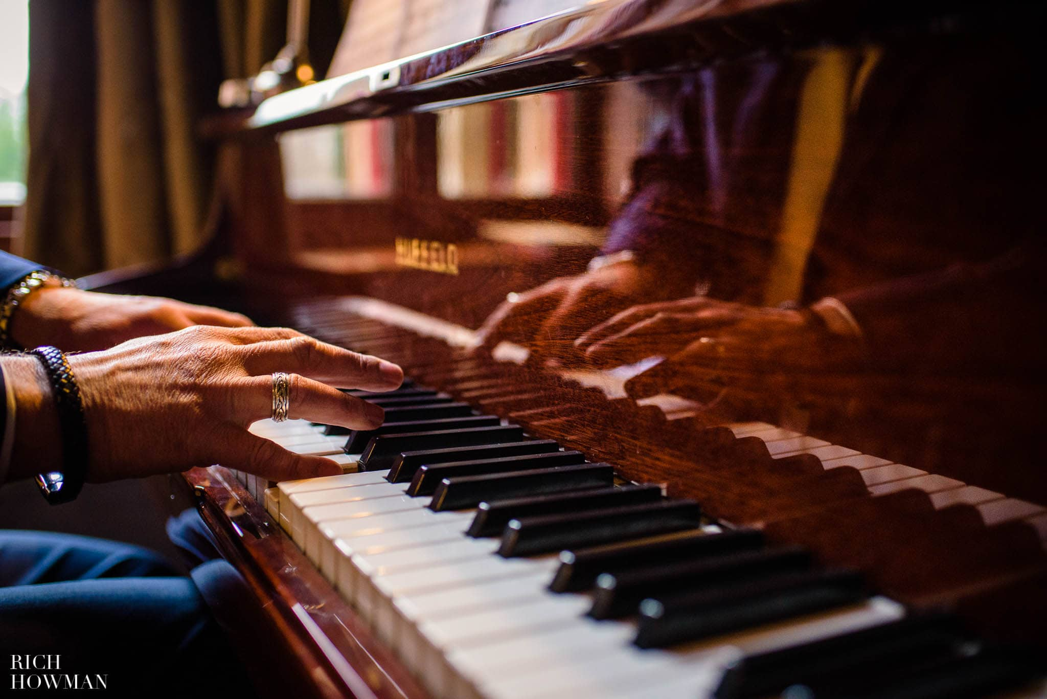 Hands playing a piano in the main hall at Huntsham Court wedding ceremony