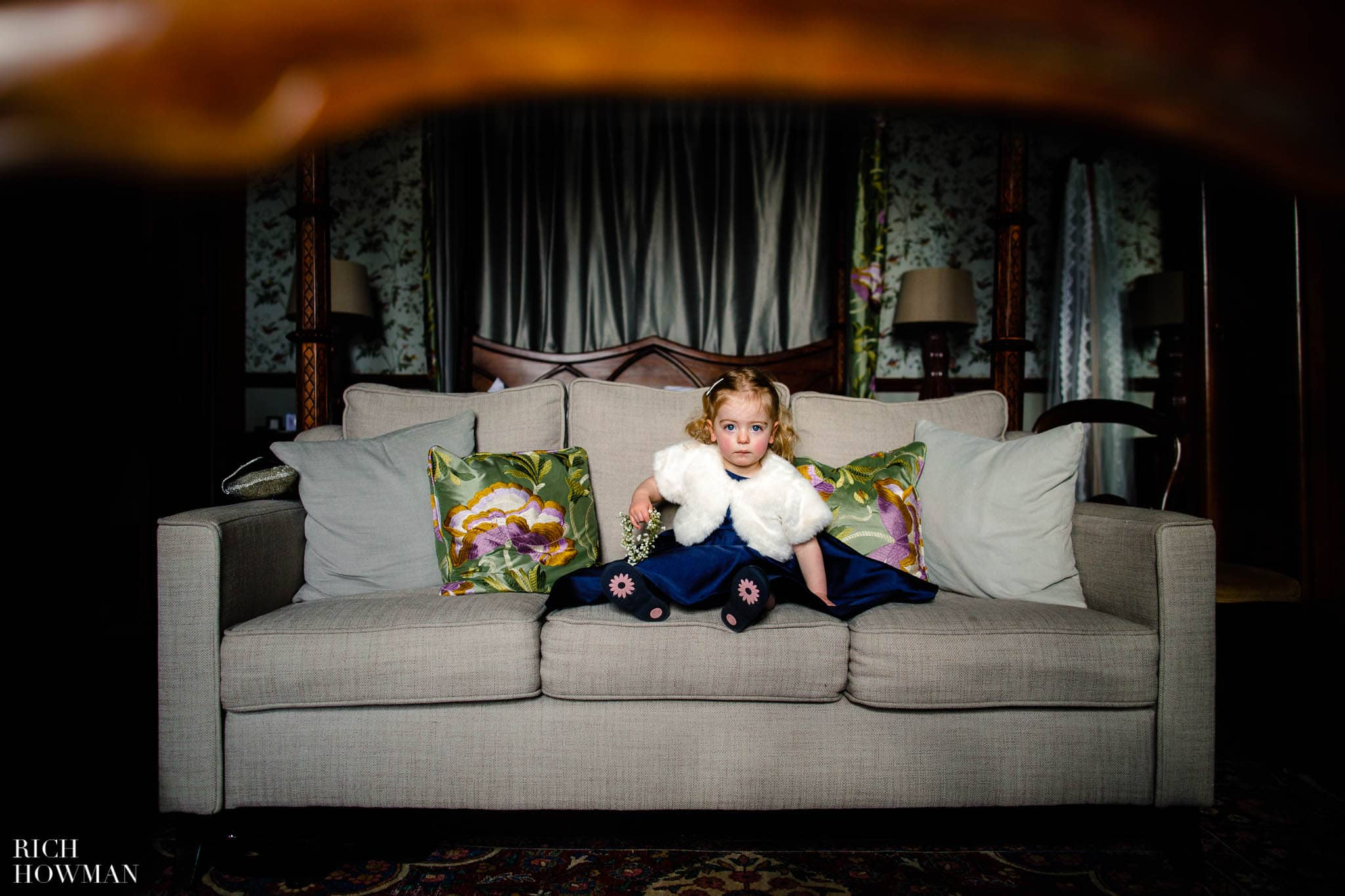 Little bridesmaid sitting on a sofa in a suite at Huntsham Court