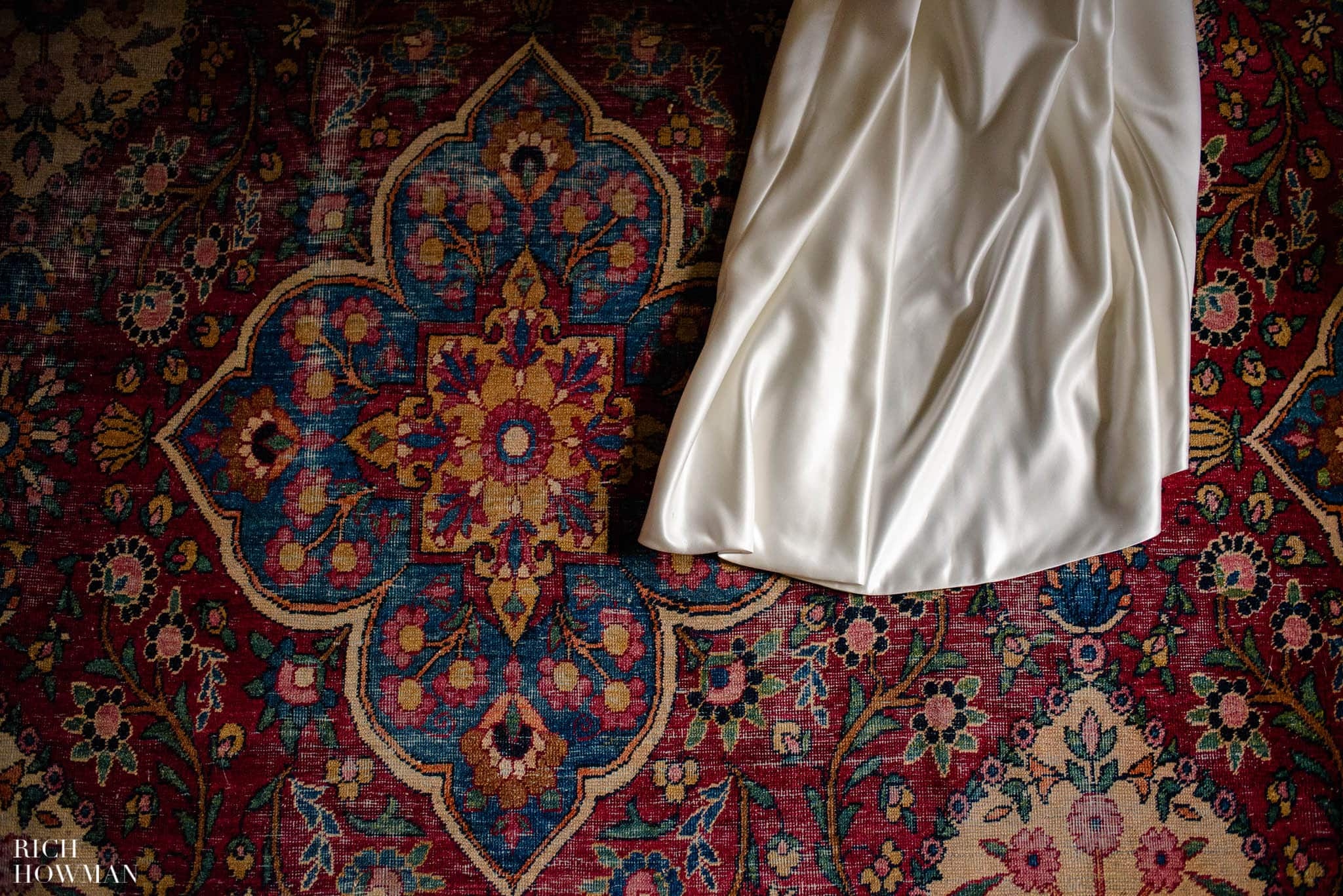 Wedding dress train laying on an oriental carpet