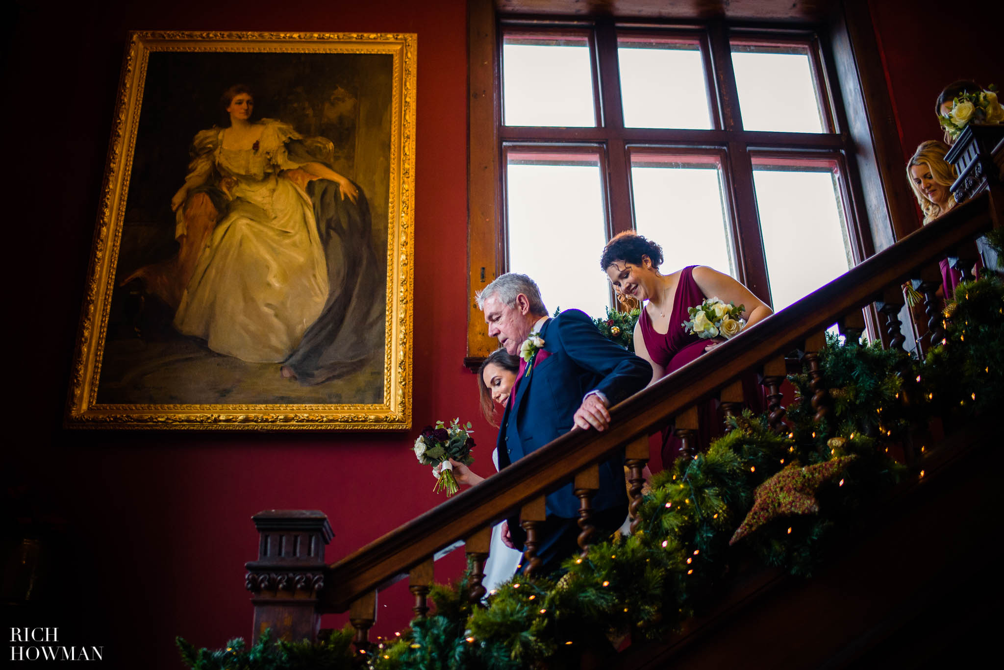 Bridal party descending the stairs at Huntsham Court before her Christmas wedding
