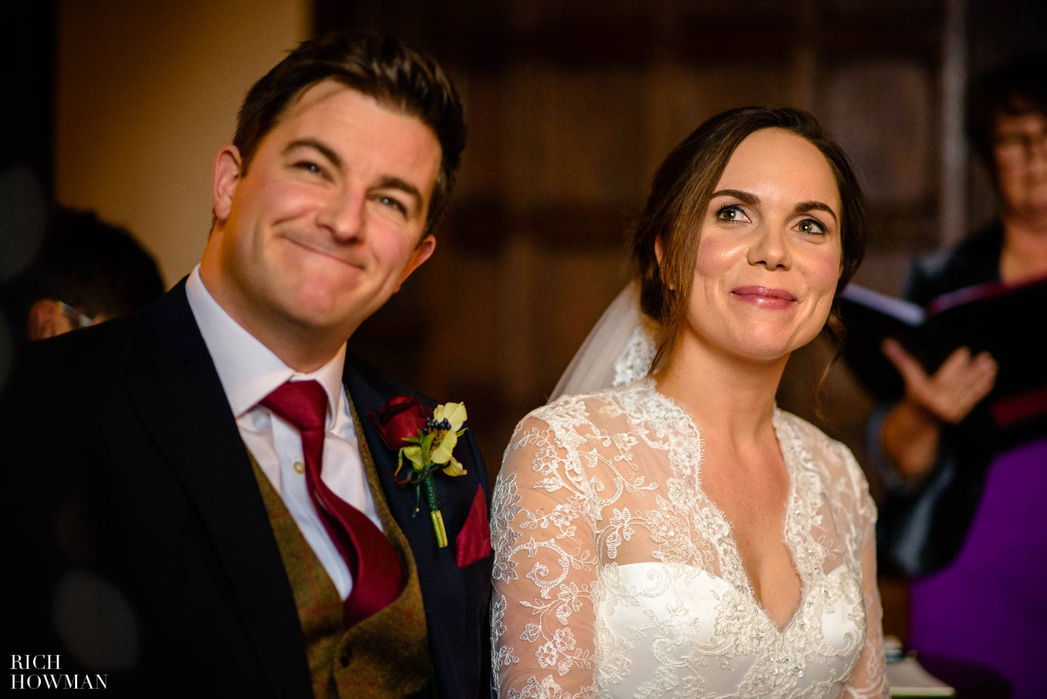 Bride and Groom smiling at the readings during their wedding ceremony at Huntsham Court