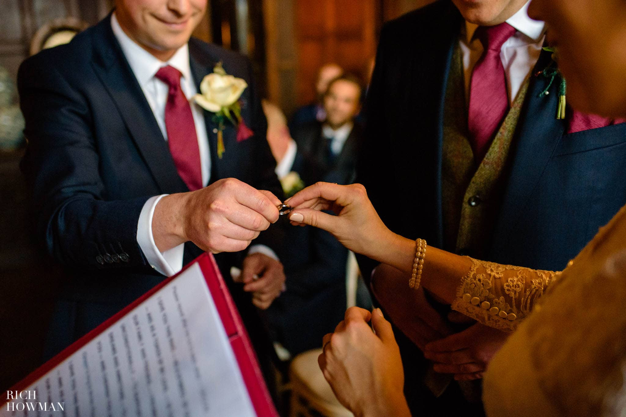 The Brides is handed the grooms wedding ring at their Huntsham Court wedding
