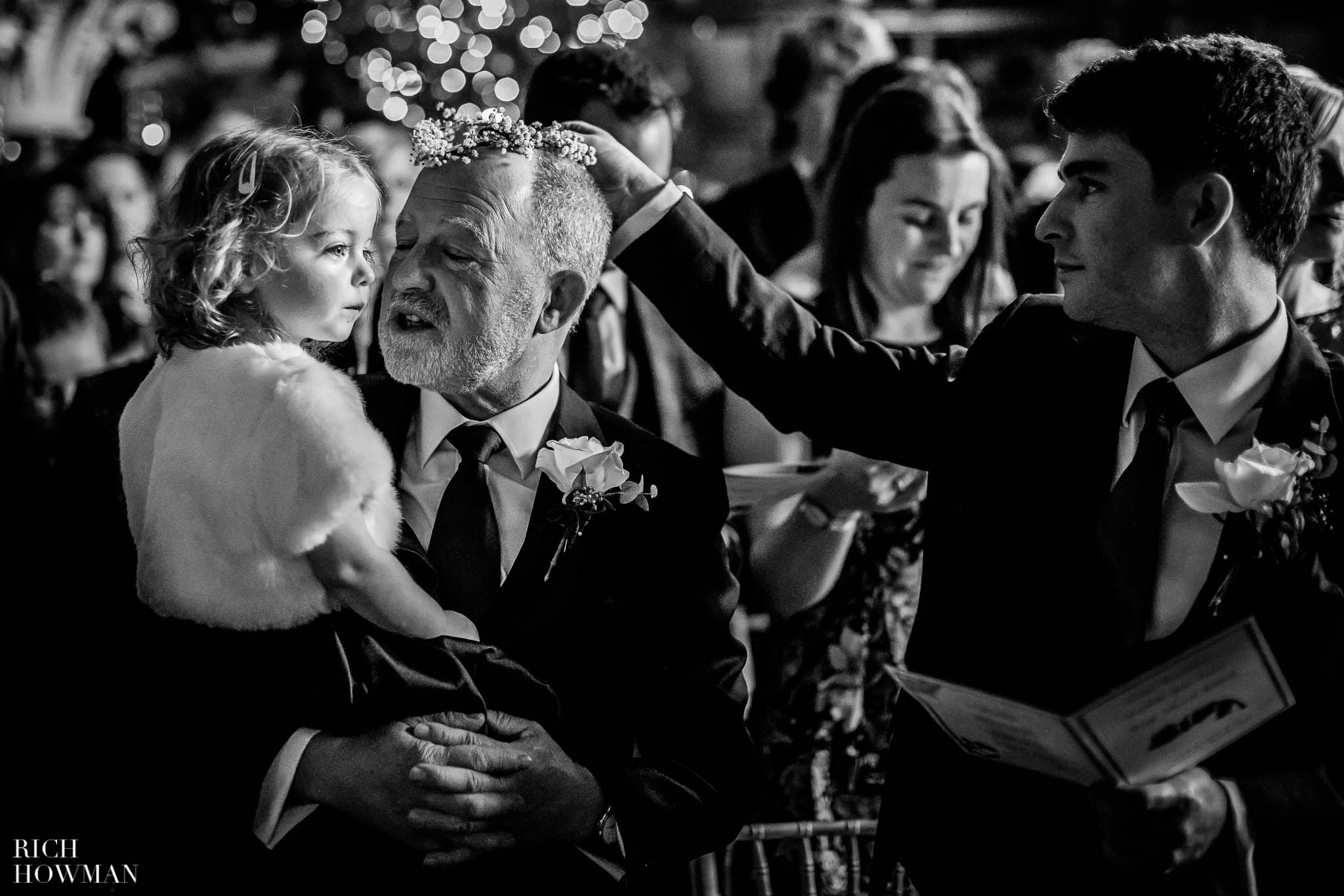 The best man places a bridesmaids flowers on the grooms fathers head