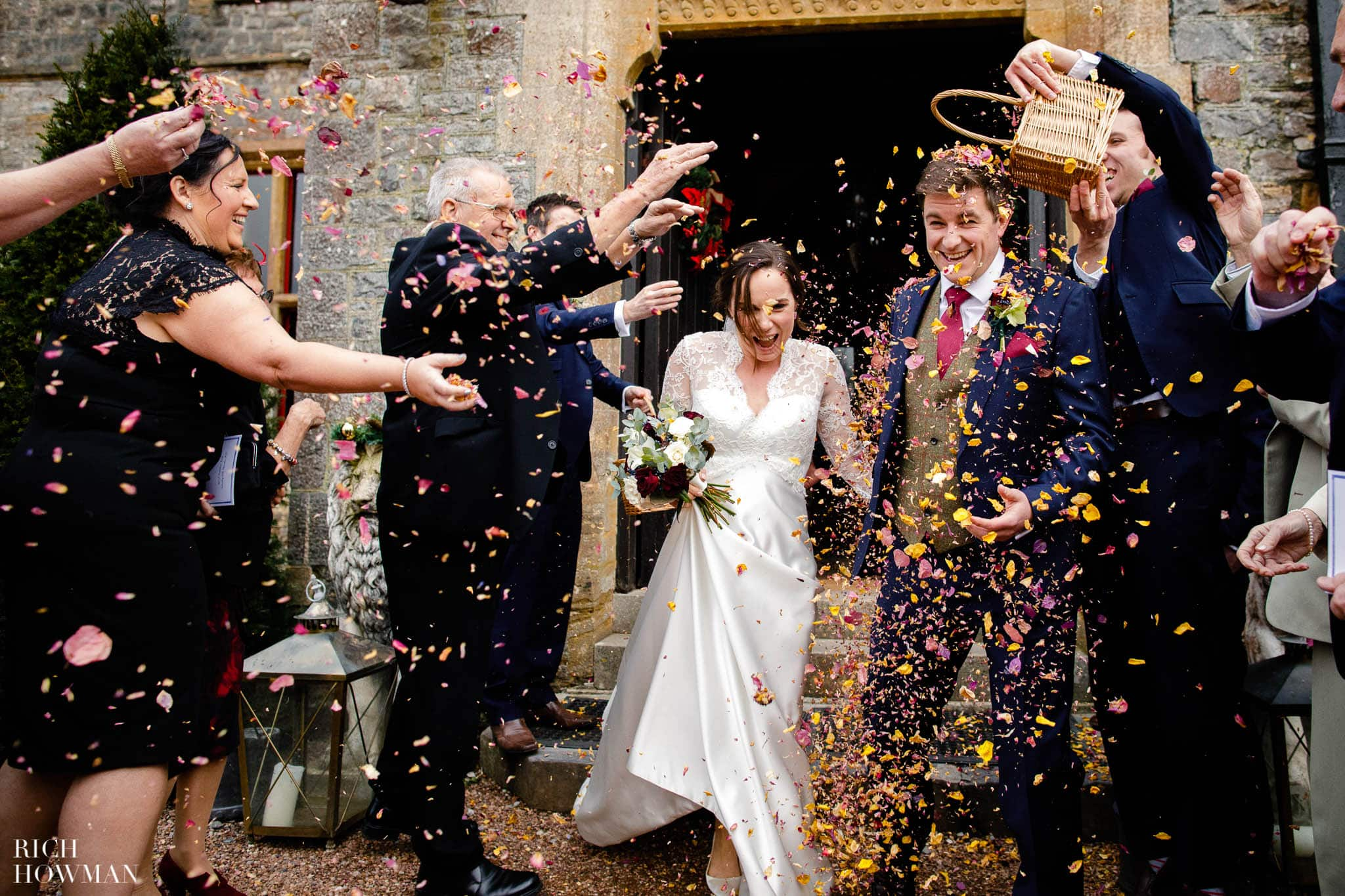 Wedding guests throw confetti captured by Huntsham Court wedding photographers