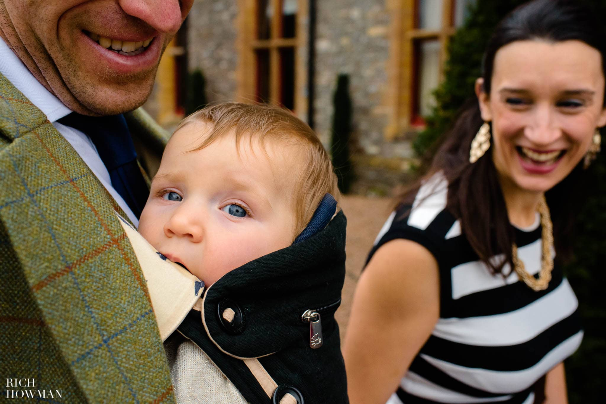 A wedding baby looks in to the camera outside Huntsham Court as his parents laugh